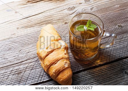 Cup of tea and croissant on wooden table with copy space. Vintage toned.