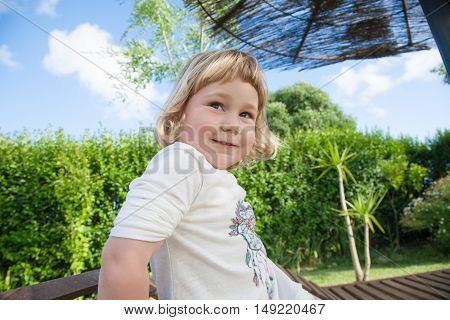 portrait funny expression of two years old blonde happy smiling child playing at garden
