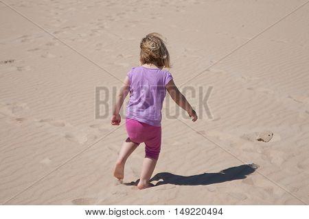Little Girl Back Walking On Sand Beach