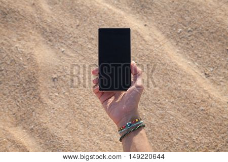 right hand of woman with colored bracelet with mobile phone smartphone black blank screen over sand beach background