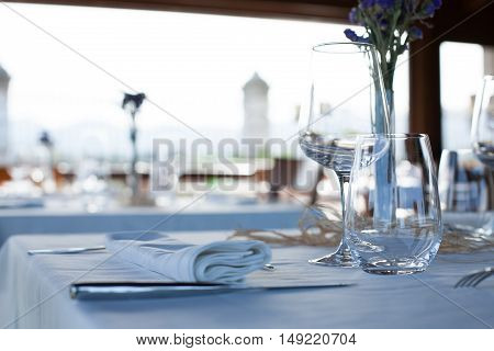 lonely table in elegant luxury restaurant interior with white tablecloth and napkins silver cutlery shiny transparent glass and wine cups crystal vase with green and purple flowers and wooden chair