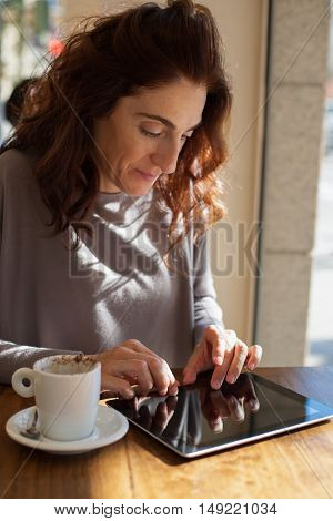 Typing Tablet In Cafe Vertical