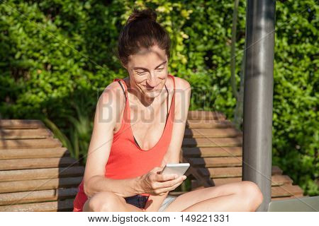 brunette smiling happy woman with red shirt sitting crossed legs using mobile phone or smartphone sitting on wooden lounge deck chair at garden