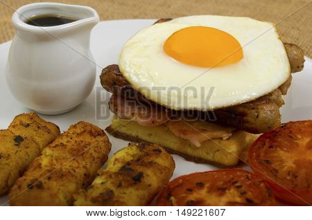 Breakfast of waffles, bacon, egg, sausage in a stack with tomato, hash browns and a jug of maple syrup