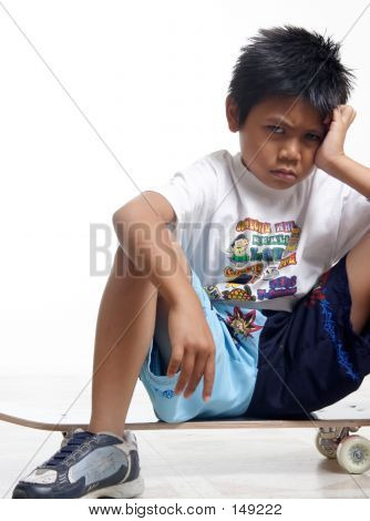Pouting Boy Sitting On His Skateboard
