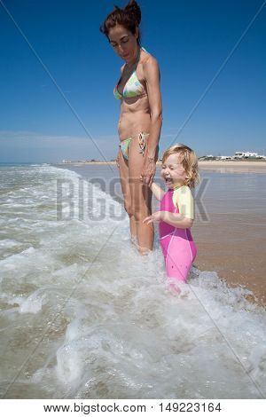 Baby And Mother Laughing With Waves