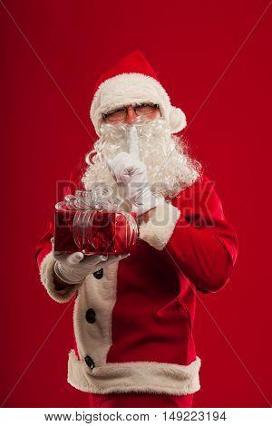 christmas Photo of kind Santa Claus giving xmas present and looking at camera. Shhhh