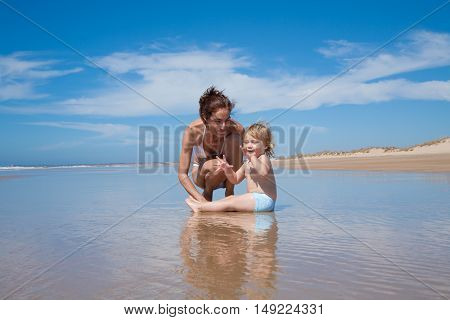 Mother And Baby Sitting At Shore