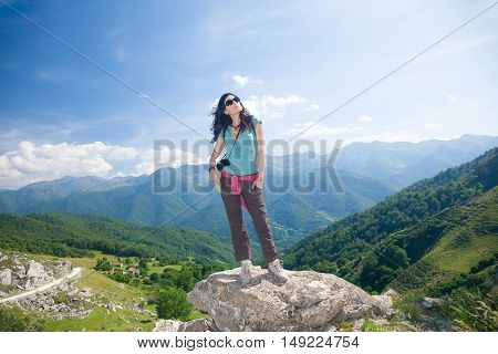 brunette sport hiking or trekking woman with green shirt brown trousers and sunglasses looking up thinking over valley and mountain in Picos de Europa natural park in Cantabria Spain