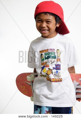 Young Boy Holding His Skateboard Behind His Back