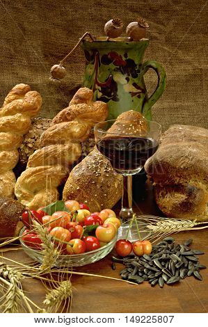Still life with bread cherrys and wine on wooden table.