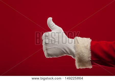 Photo of Santa Claus gloved hand in thumbs up gesture. fingers. christmas