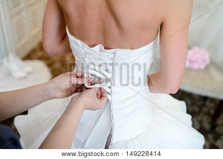 Bridesmaid is lacing white wedding dress for beautiful bride. Beauty model girl in bridal gown for marriage. Female portrait. Woman with lace veil. Cute lady indoors