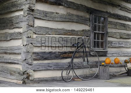 Simple exterior of an old-time general store.  A bicycle leans near a window, with pumpkins on a bench nearby.