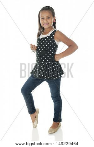 A pretty elementary girl standing and sassy in her polka dot top and jeans.  On a white background.