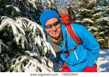 Portrait of hiker in the winter forest among the snow-covered pine trees. Sunny winter day.