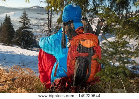 Hiker is resting in the winter forest among the snow-covered pine trees admires the view of winter mountains. Back view.