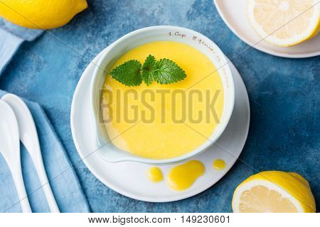 Lemon curd in ceramic bowl with fresh lemons on a blue napkin background. Top view Selective focus