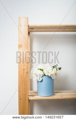 Bouquet of white hydrangeas in round  blue box on wooden shelf. Home interior decoration