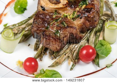 Grilled steak with roasted asparagus and cherry tomatoes with sauce close-up on a white plate