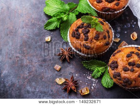 Food and drink, seasonal concept. Homemade chocolate chip muffins with green mint for breakfast on a grunge rusty pan. Selective focus, copy space background