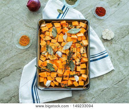 Chopped orange butternut squash on baking sheet with herbs/Diced Squash