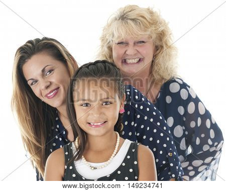 Close-up image of three generations of women -- an elementary child, her mother and grandmother, all wearing polka dot tops.  On a white background.