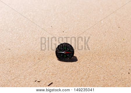 Compass on the sea sand at the beach