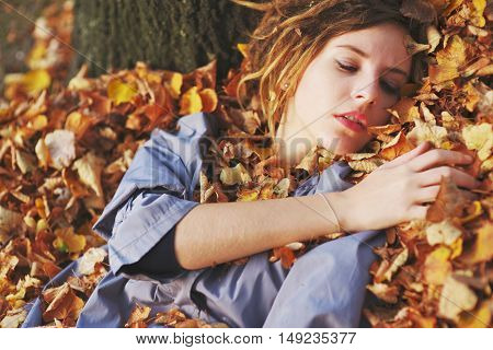 Cute young girl lying on the armful of yellow autumn eyes closed.