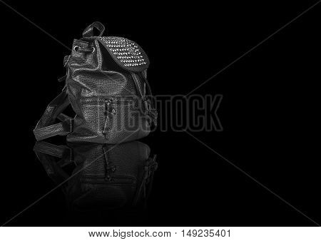 luxury leather black bag side view with diamond studs and dual zipper for women on black background and reflection shadow isolated included clipping path