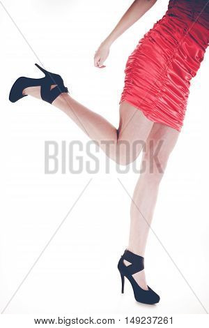 Stylish young woman wear fashionable clothes. Long legs in black high heels. Girl in short red dress.