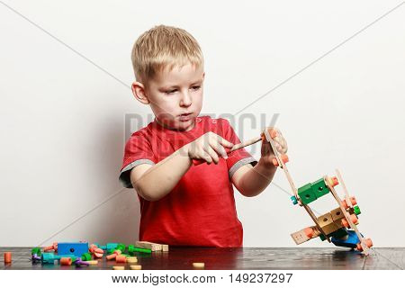 Spending free time play and education for children. Little boy in red shirt play with colorful toy on table.