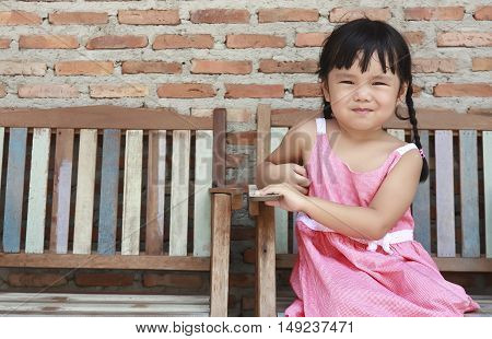 cute asian children pigtail and smile sit on the old or vintage wood chair and brick wall background on street