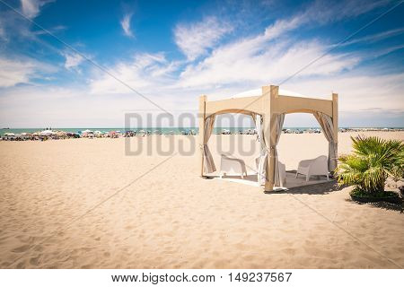 Gazebo sandy colored with white chairs on the beach.