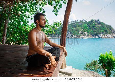 Man in meditation in a wooden hut in Thailand
