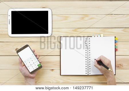 people holding and looking calculator on smartphone display and tablet with writing diary or notebook on top view wood table included clipping path on smartphone display only