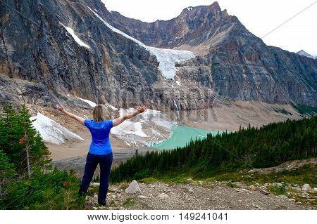 Woman on mountain top above glacier lake. British Columbia. Canada.