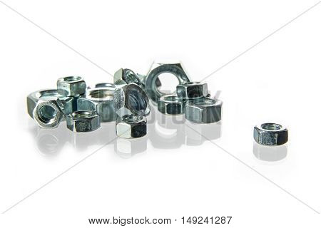 nuts of steel for machine screws on a heap isolated with reflection on a white background concept for construction crafts and industry closeup with selected focus and narrow depth of field