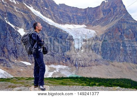 Man Hiker with Angel Glacier and lake view. Edith Cavell Meadows. Alberta. Canada.