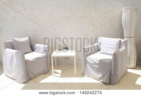 Terrace lounge with white armchairs and wall in a summer resort .