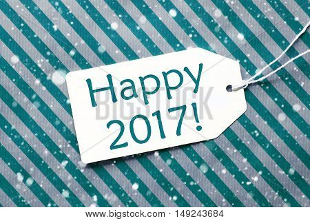 One Label On A Turquoise Striped Wrapping Paper. Textured Background With Snowflakes. Tag With Ribbon. English Text Happy 2017 For Happy New Year Greetings