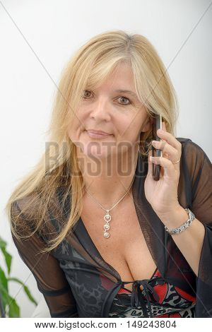 a mature blond woman talking on mobile phone
