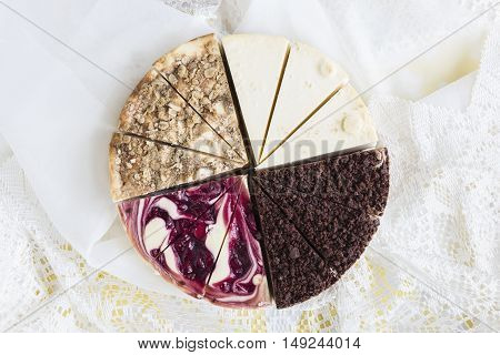 horizontal image of an assortment of sliced cheese cakes set together in a pie form on a white nylon background with room for text.