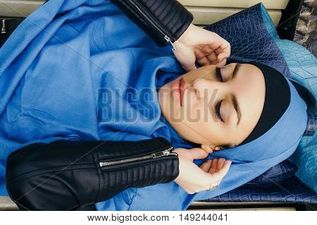 young girl in a blue scarf lying on a park bench