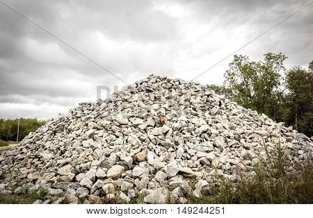 horizontal image of a large pile of rocks heaped up to a peak under a very cloudy grey sky in the summer with room for text.