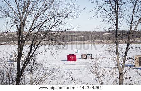 horizontal image of ice fishing huts sitting on a frozen lake covered with snow with some bare trees in the foreground framing the image in the winter.