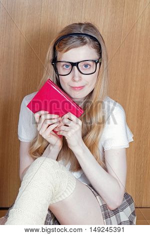 Young blonde school girl holding closed book