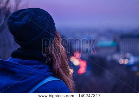 Girl hipster looking at winter evening cityscape purple violet sky and blurred city lights
