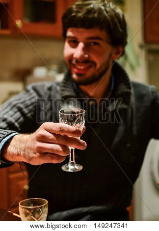 Young unshaven man holding glass of strong alcoholic drink vodka looking at camera. Cheers