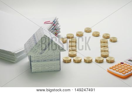 House and pile of gold coins with calculator and pile overload document with colorful paperclip on white background.